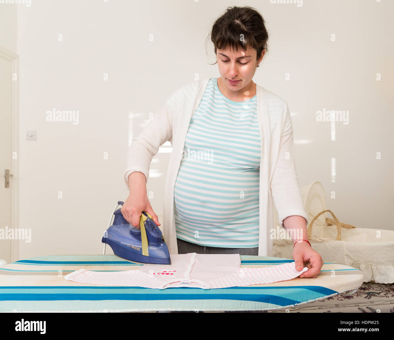Pregnant woman ironing baby clothes in preparation for baby's arrival, England, UK - Stock Image