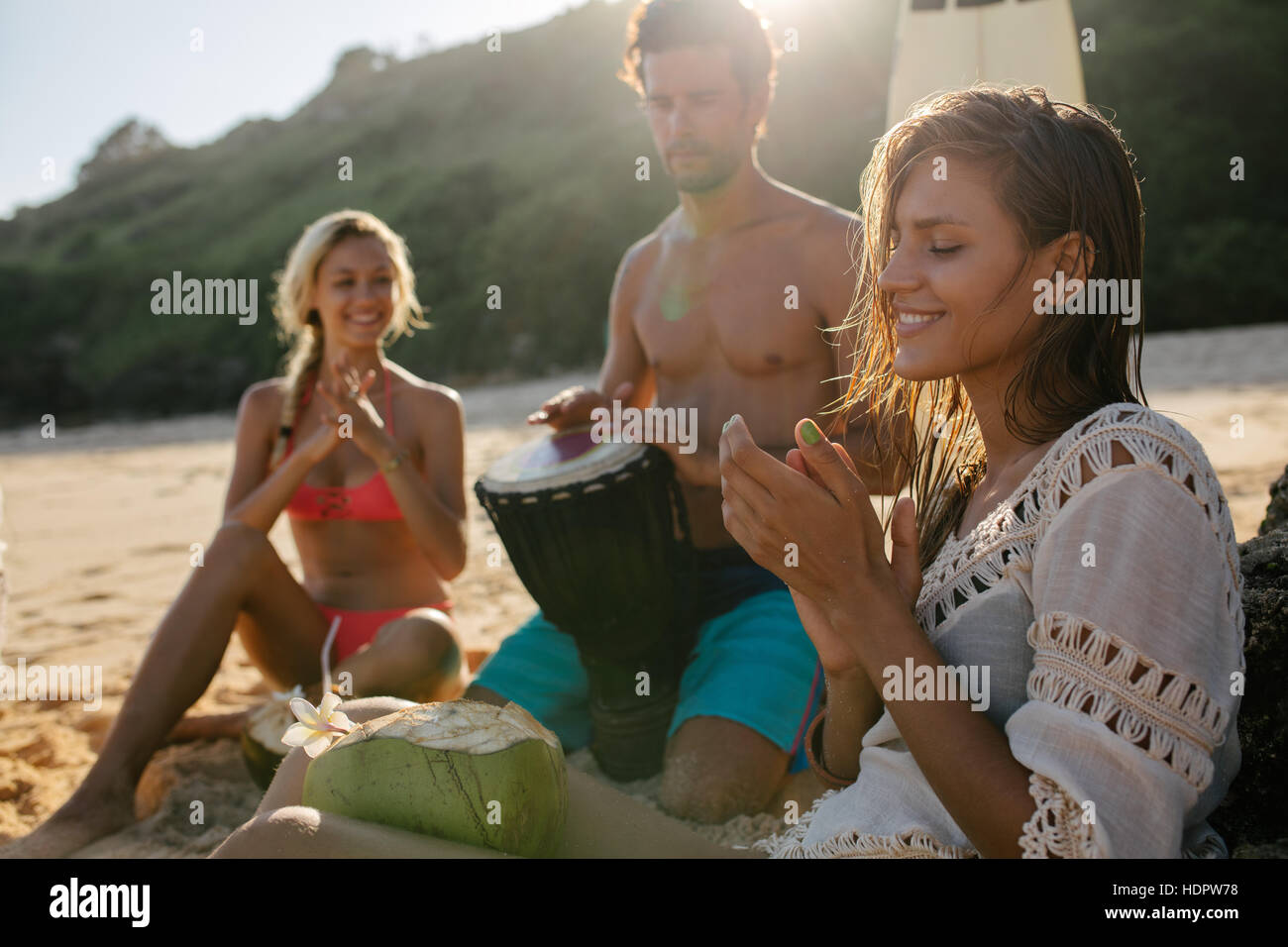 Young woman enjoying holidays with her friends on the beach. Women clapping and man playing dumbek. Stock Photo