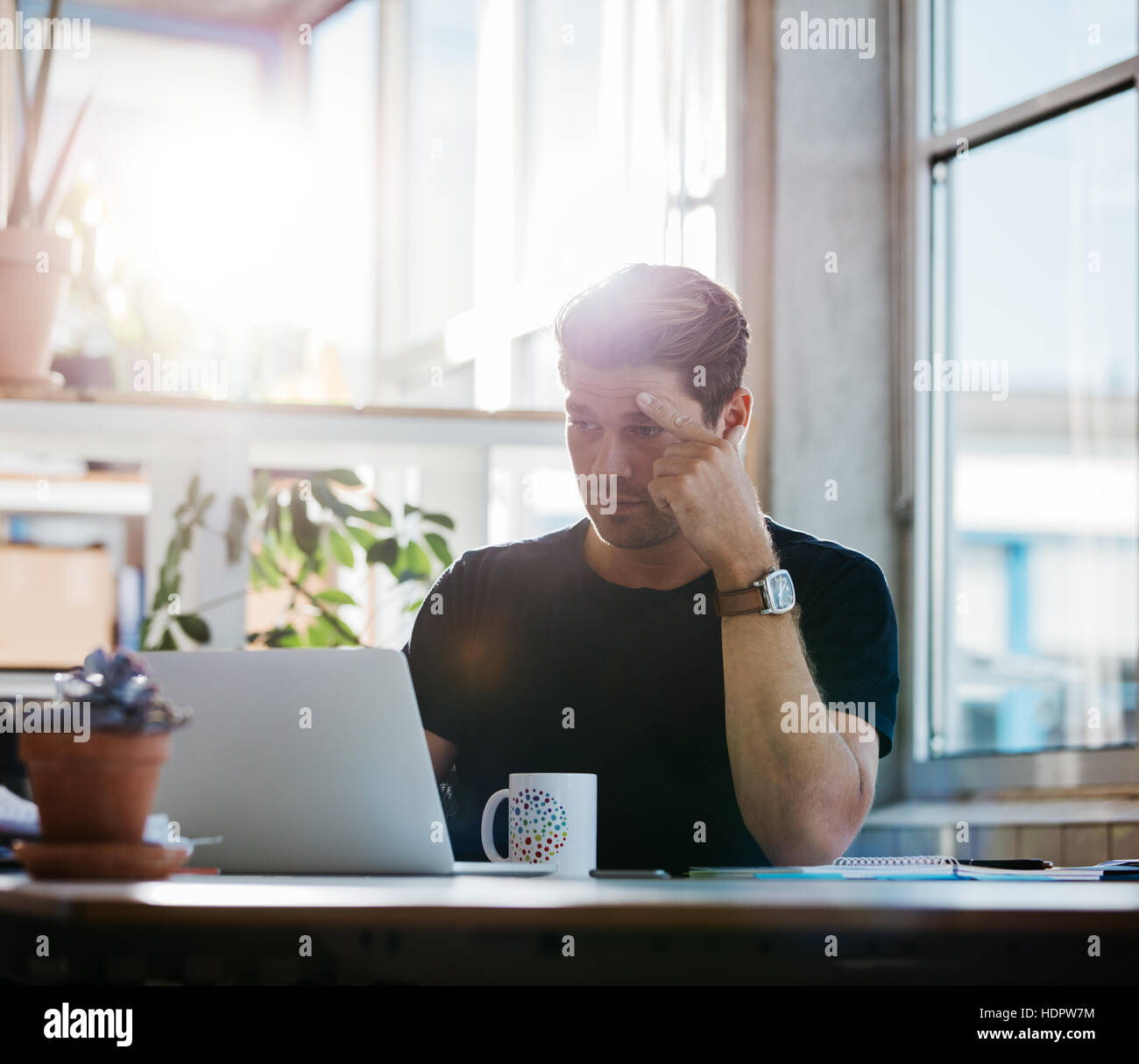 Young business man with stress looking at his laptop in the office. Male executive concentrating at work. - Stock Image