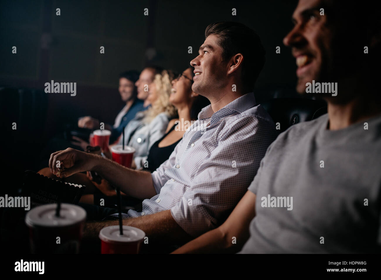 Group of young people sitting in cinema hall watching movie. Multiracial group of friends watching movie in theater. Stock Photo