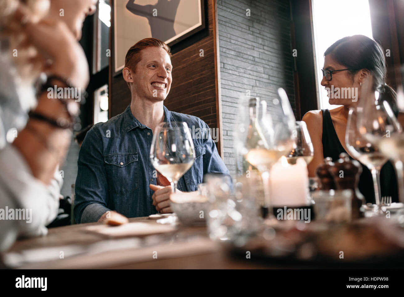 Happy young man with friends at cafe. Young people enjoying dinner at a restaurant. Stock Photo
