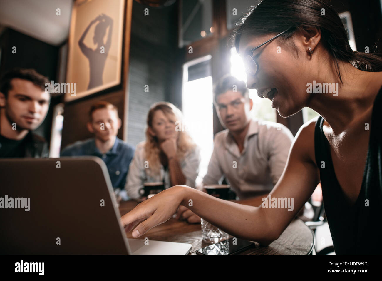 Young woman pointing at laptop and discussing with friends. Group of young people at cafe looking at laptop computer. - Stock Image