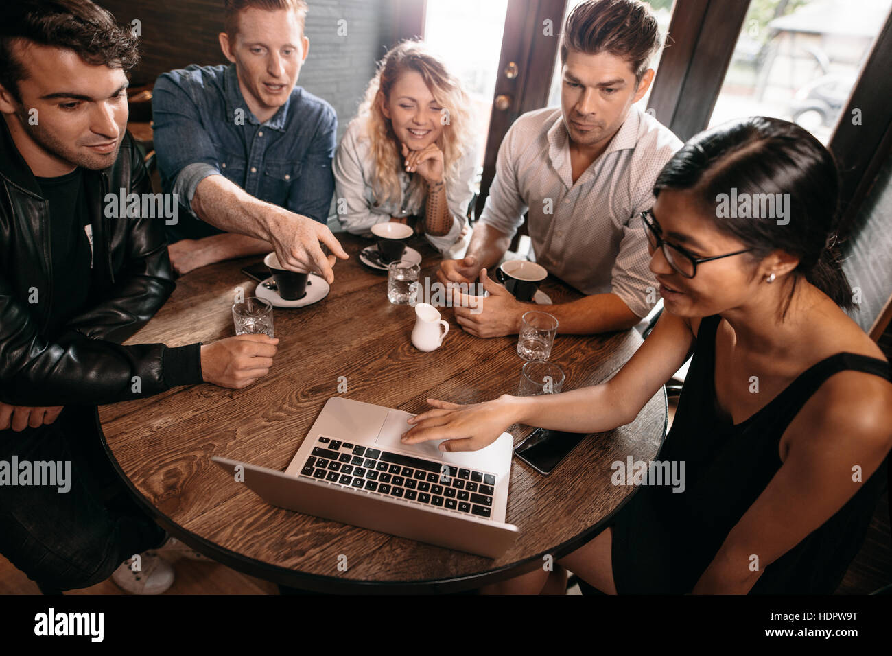 Diverse group of friends sitting together at cafe with man pointing at laptop. Five young people hanging out at Stock Photo