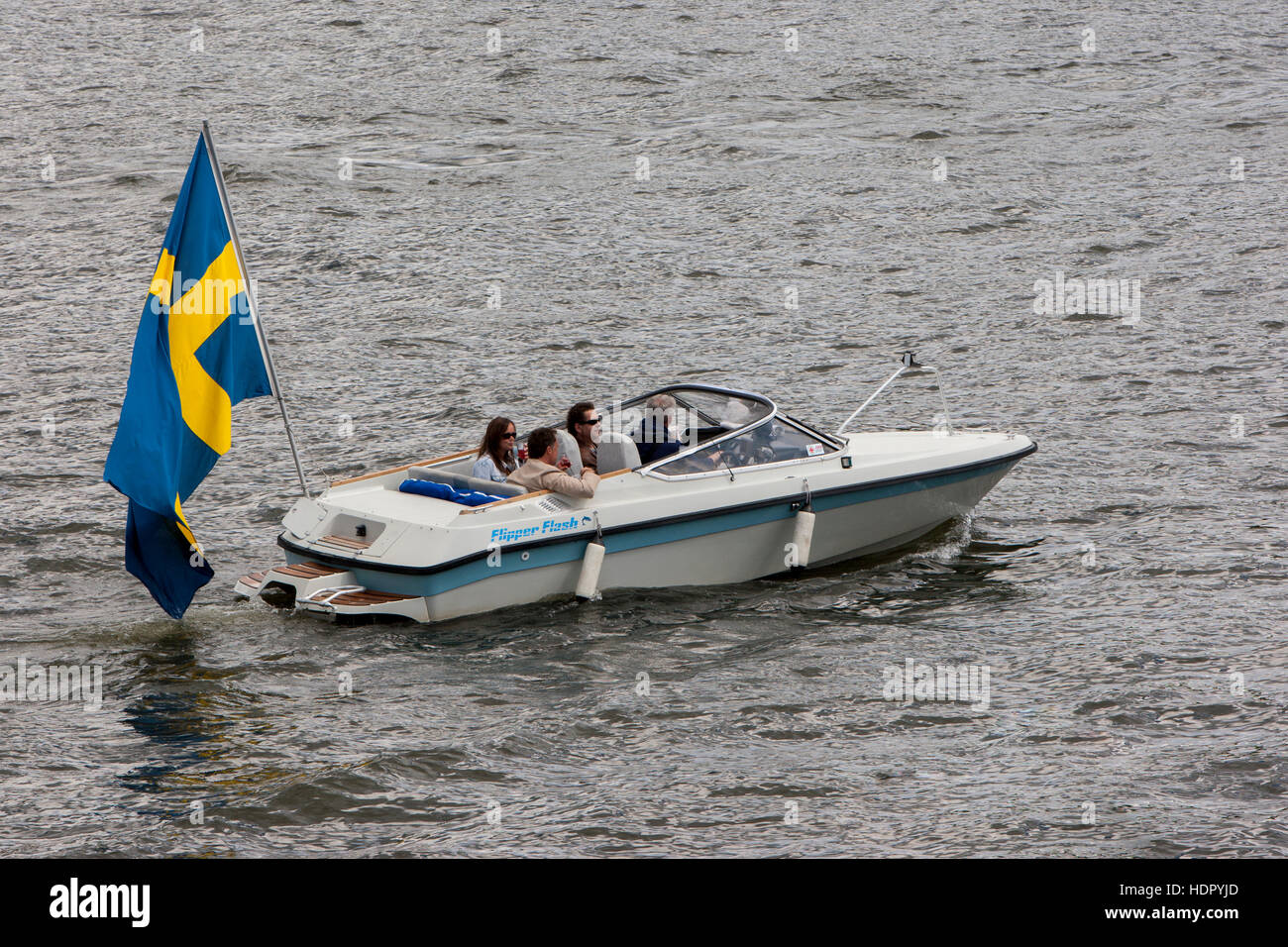 A boat with very large Swedish flag. - Stock Image