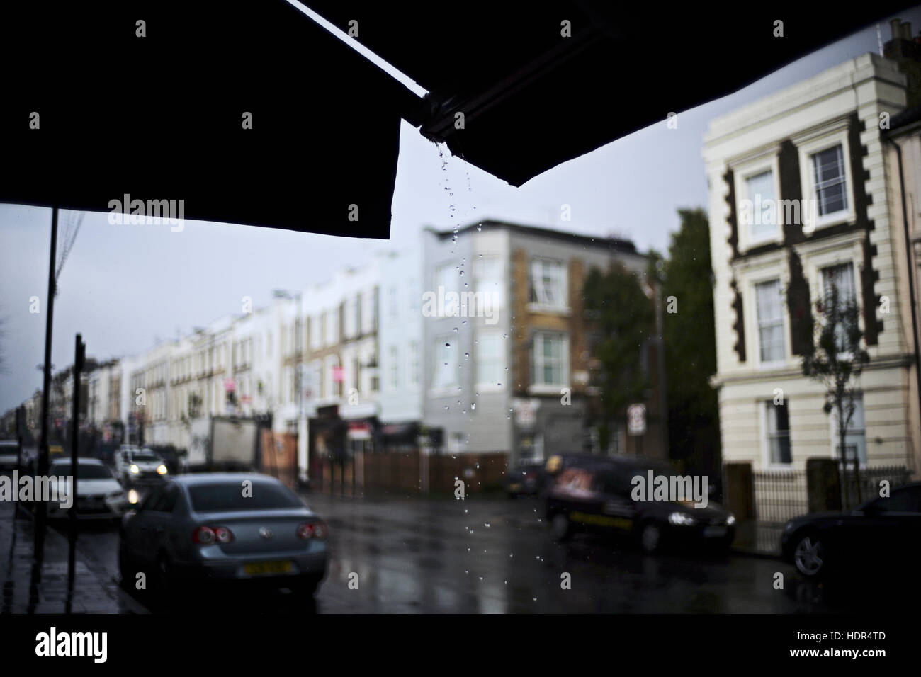 Drops of water falling from shop awning on a gloomy urban daylight rain storm - Stock Image