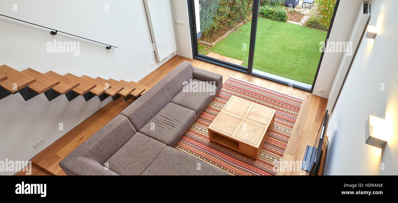Modern living room with large windows and view on a automnal garden - Stock Image