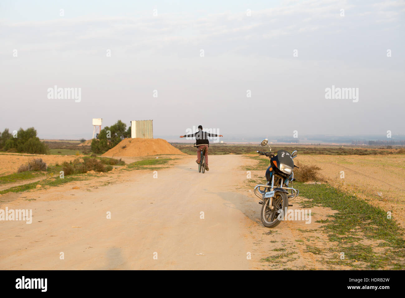 A young man cycles close to the Israeli border with Gaza, during a protest. - Stock Image