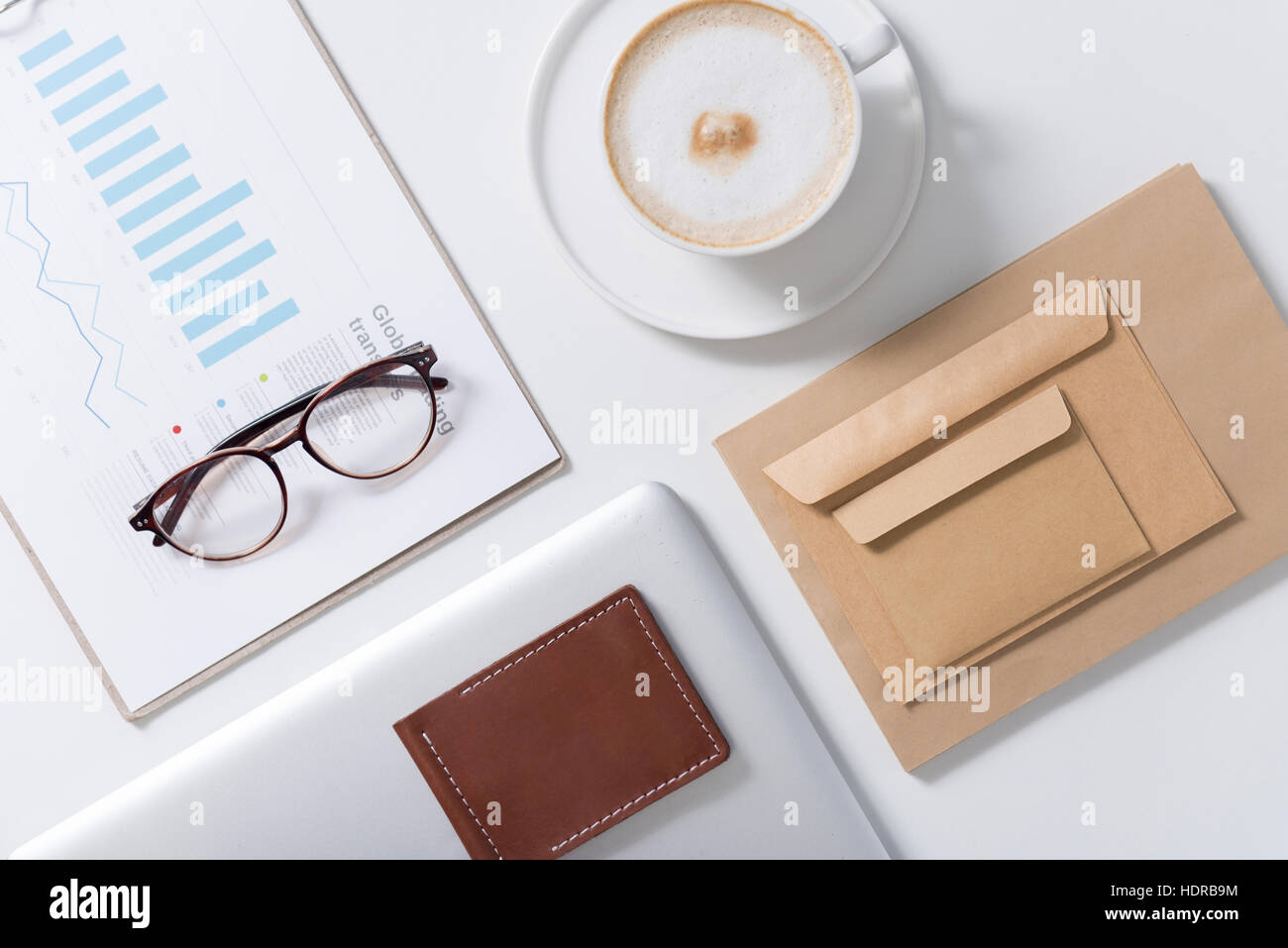 Eyeglasses lying on statistical data documents - Stock Image