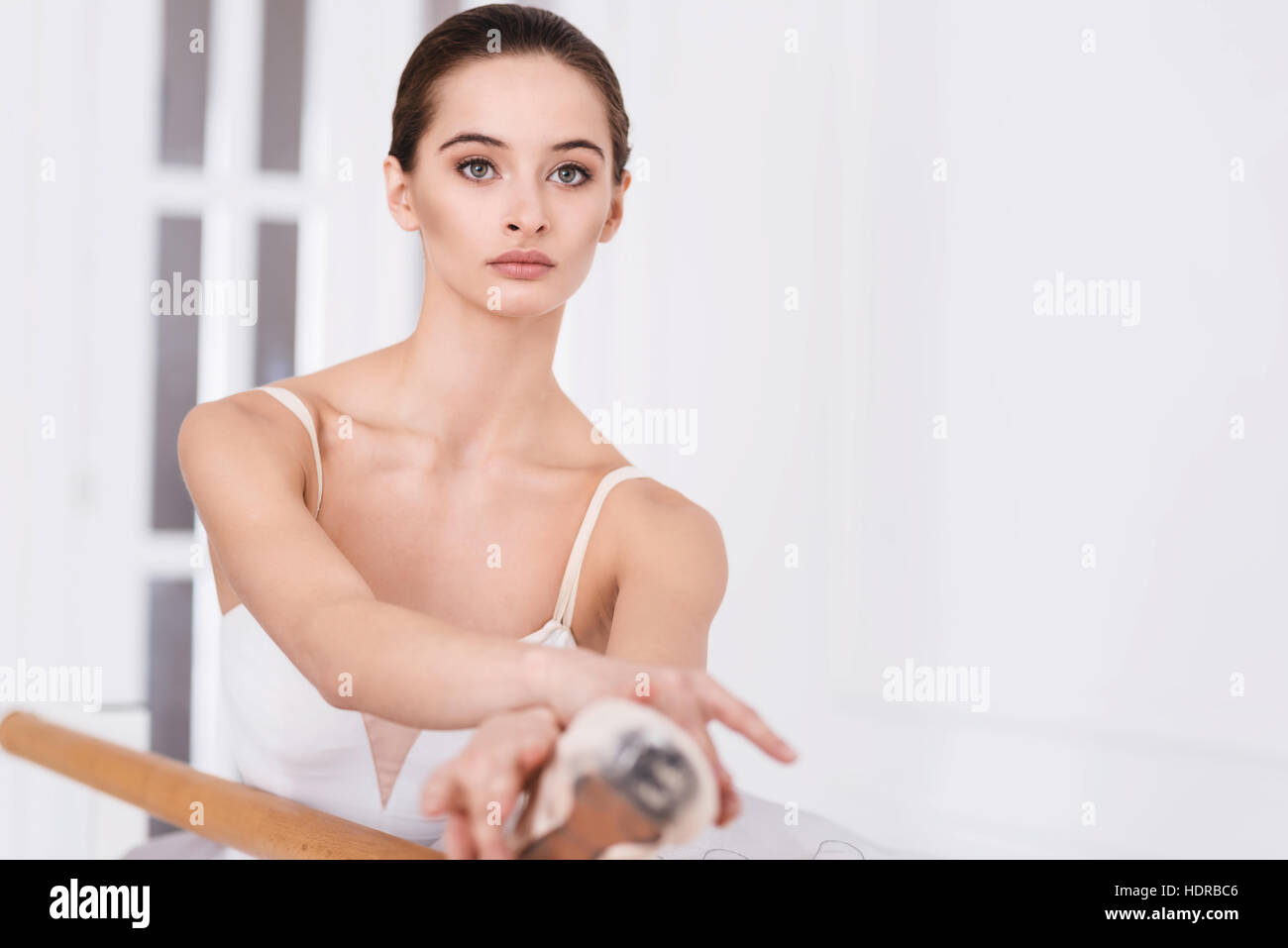 Serious ballet dancer crossed her arms on the leg - Stock Image