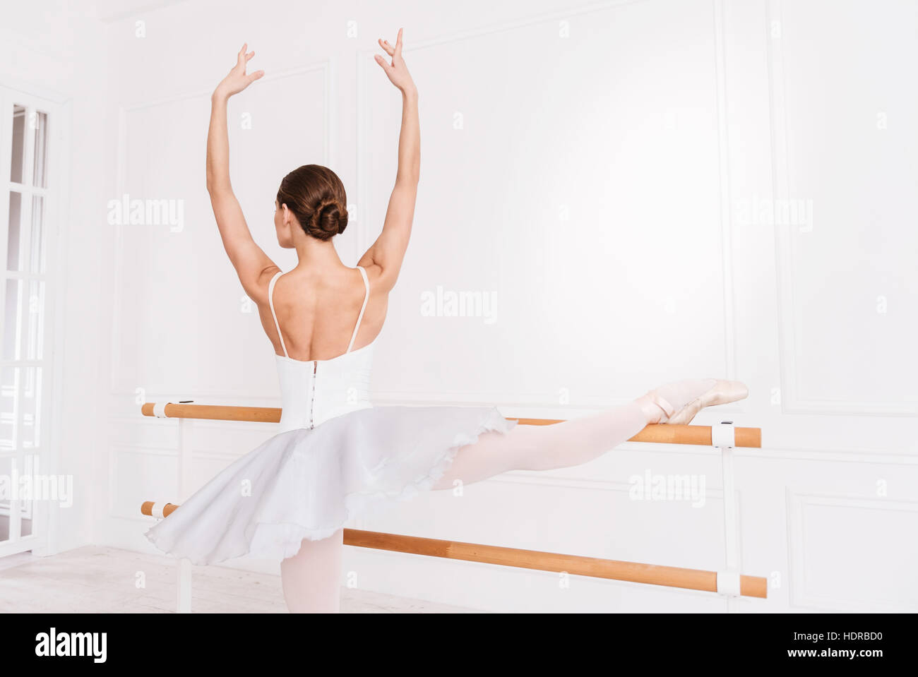 Tender ballerina keeping arms like in fifth position - Stock Image