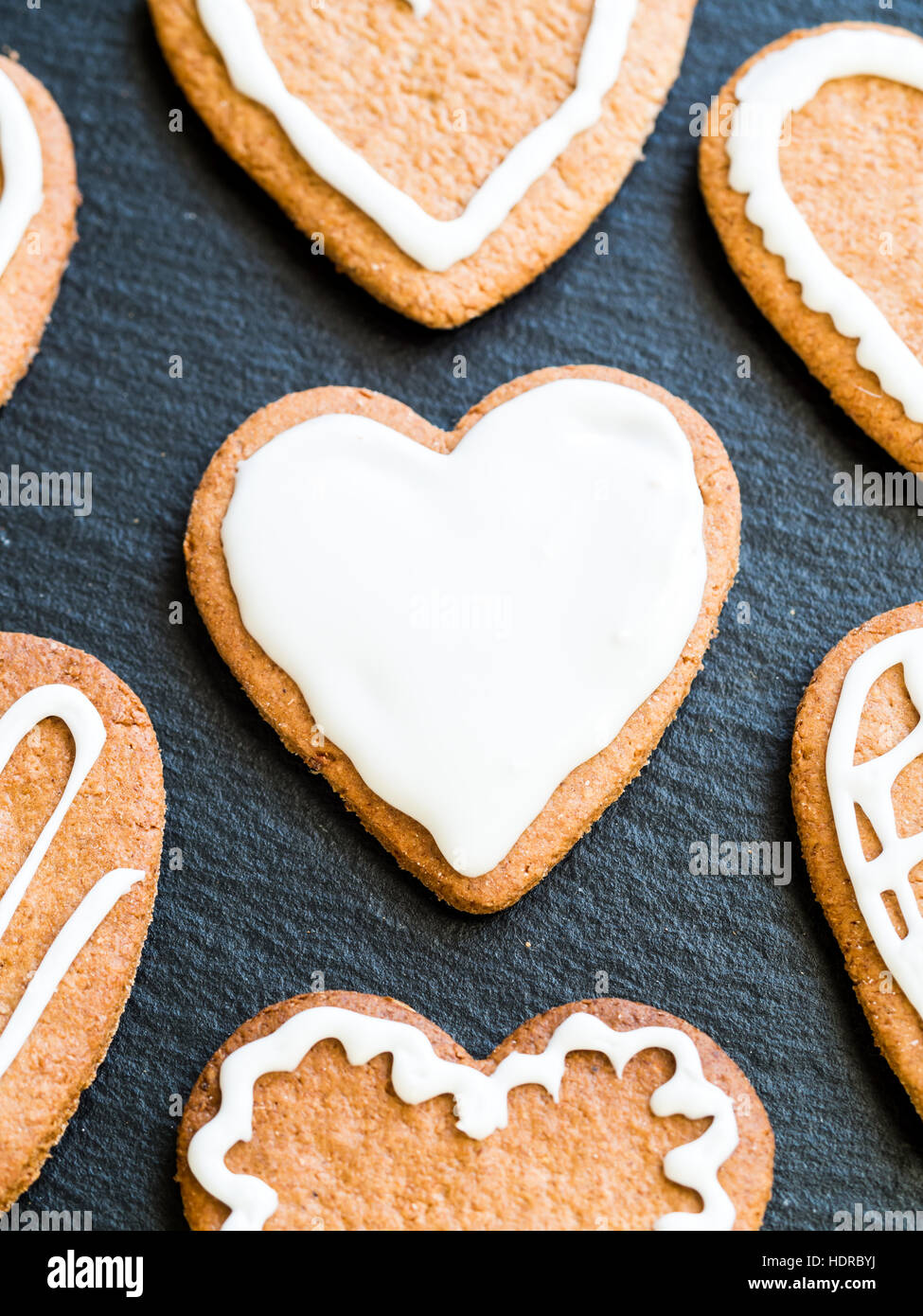 Heart-shaped Christmas gingerbread cookies on a dark background. - Stock Image