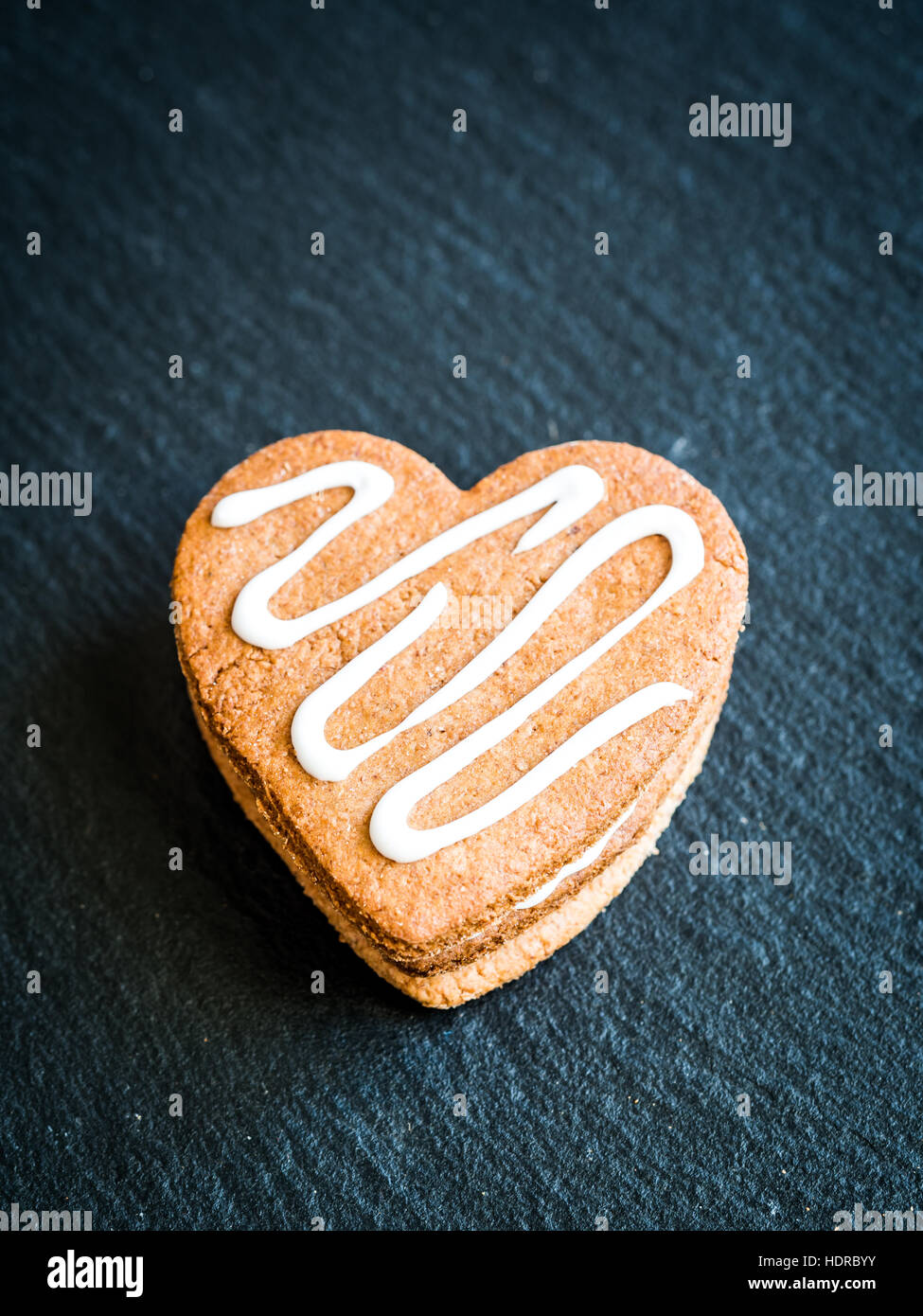 Heart-shaped Christmas gingerbread cookies arranged in a pile on a dark background. - Stock Image