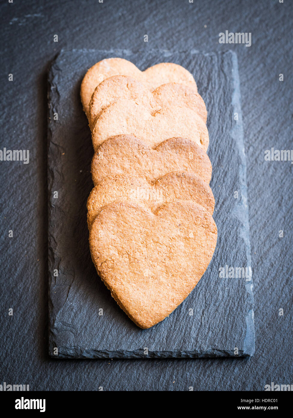 Heart-shaped gingerbread cookies on a dark background. - Stock Image