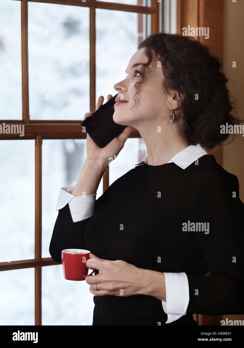 Woman with a cup of coffee talking on the phone by a window with a snowy winter scenery behind it. Apple iPhone Stock Photo
