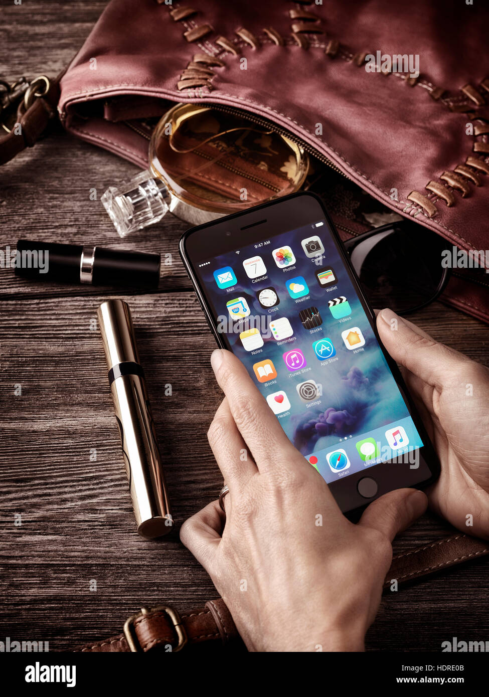 Woman hands holding Apple iPhone 7 Plus with her purse, makeup and accessories on the table conceptual still life - Stock Image