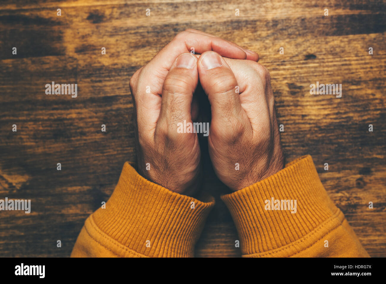 Top view of religious male crossed hands in prayer, christian religion practice - Stock Image