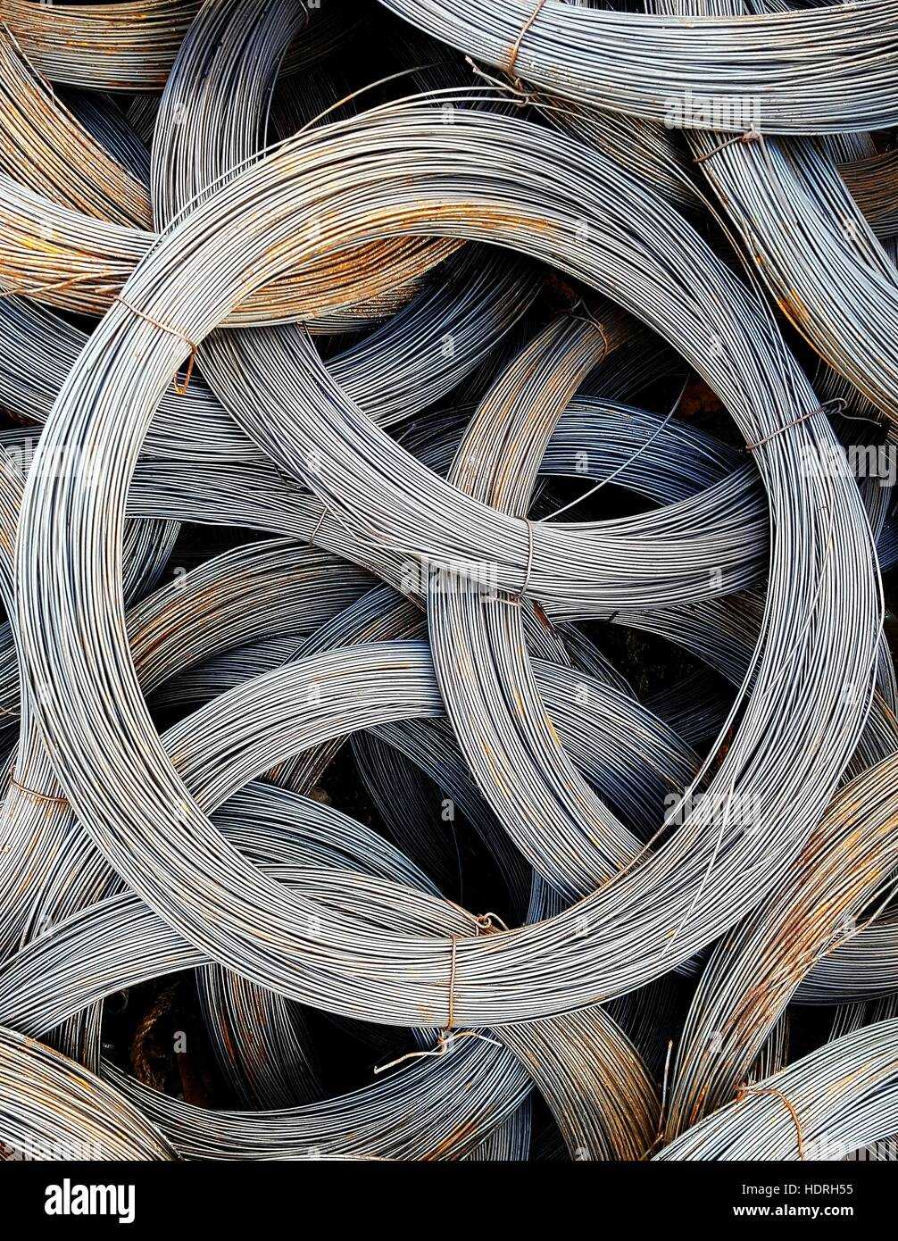 Coils of old galvanized wires with traces of rust - Stock Image