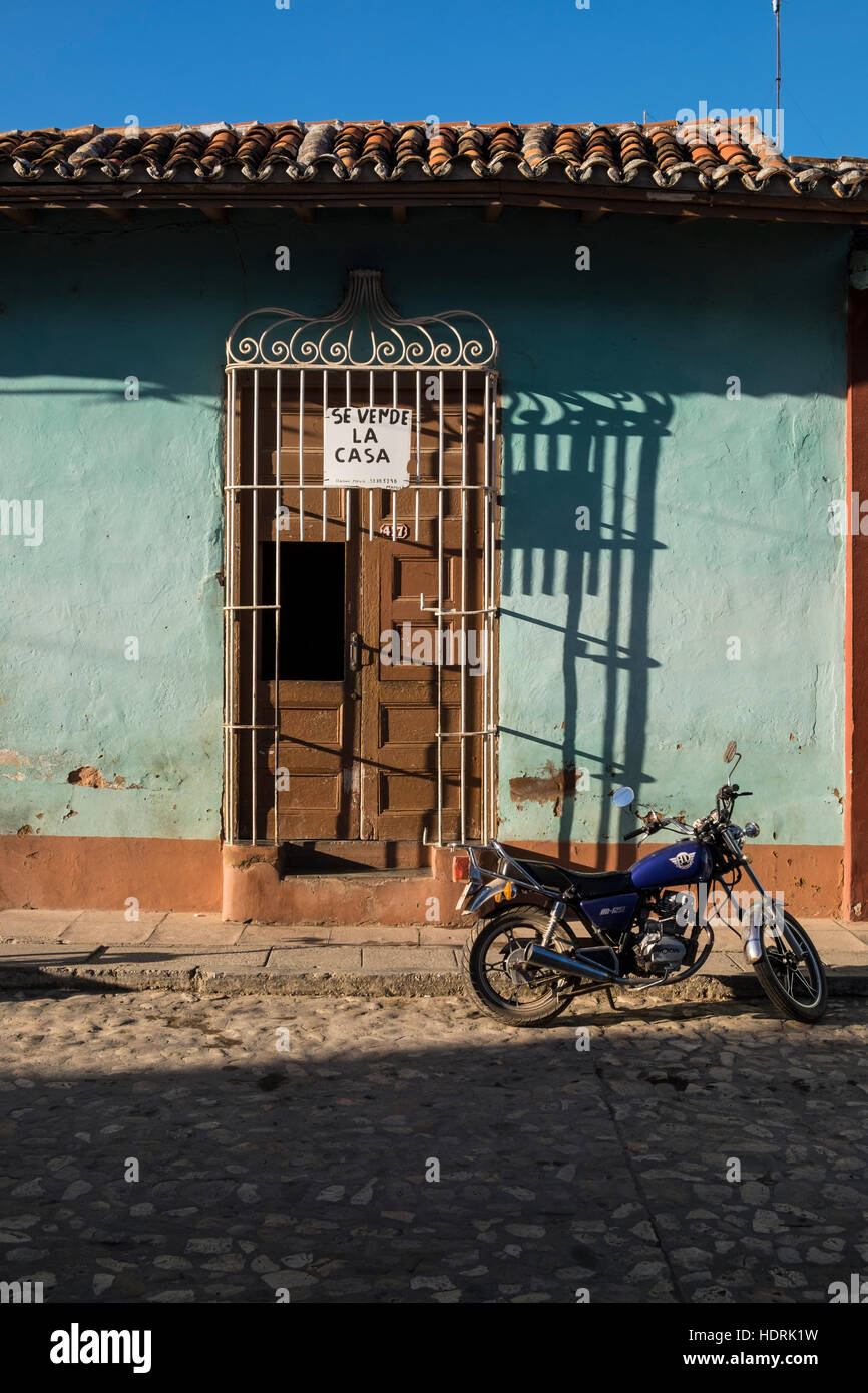 House for sale and motorcycle on a cobbled back street in Trinidad, Cuba - Stock Image
