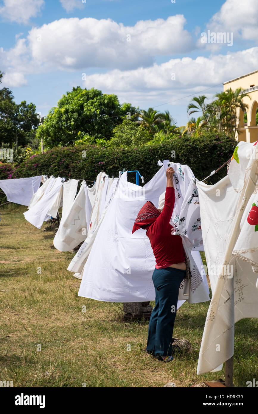 Woman pegging tablecloths to a line, linen for sale at Manaca Iznaga, Trinidad, Cuba - Stock Image