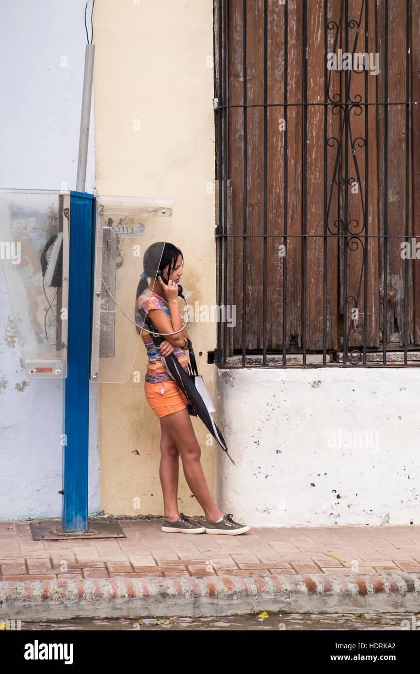 Young girl talking on a public telephone in the Plaza del Carmen, Camaguey, Cuba - Stock Image