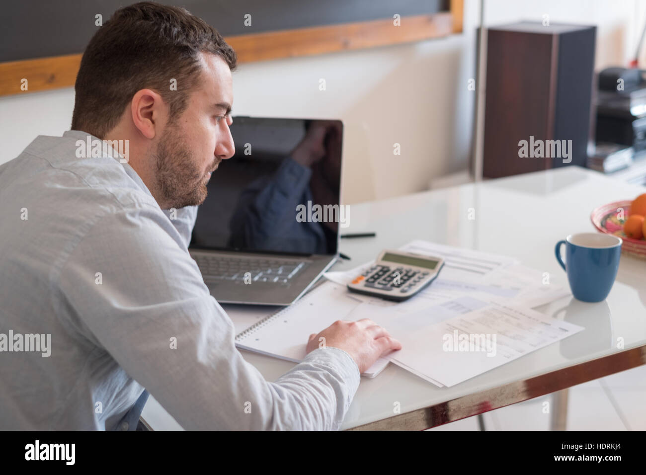 Frustrated man calculating bills and tax  expense - Stock Image