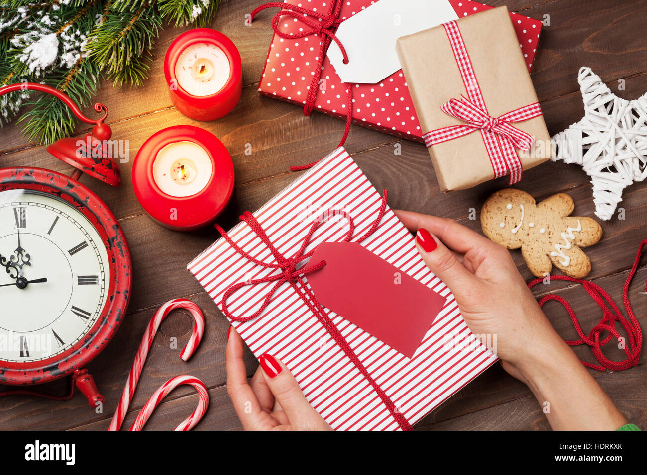 female hands holding christmas gift above wooden table top view xmas gift wrapping - Xmas Present