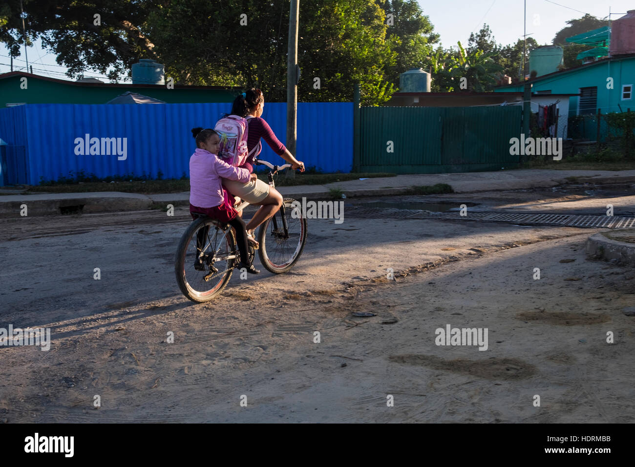 Woman taking child to school on the back of a bicycle, Vinales, Cuba - Stock Image