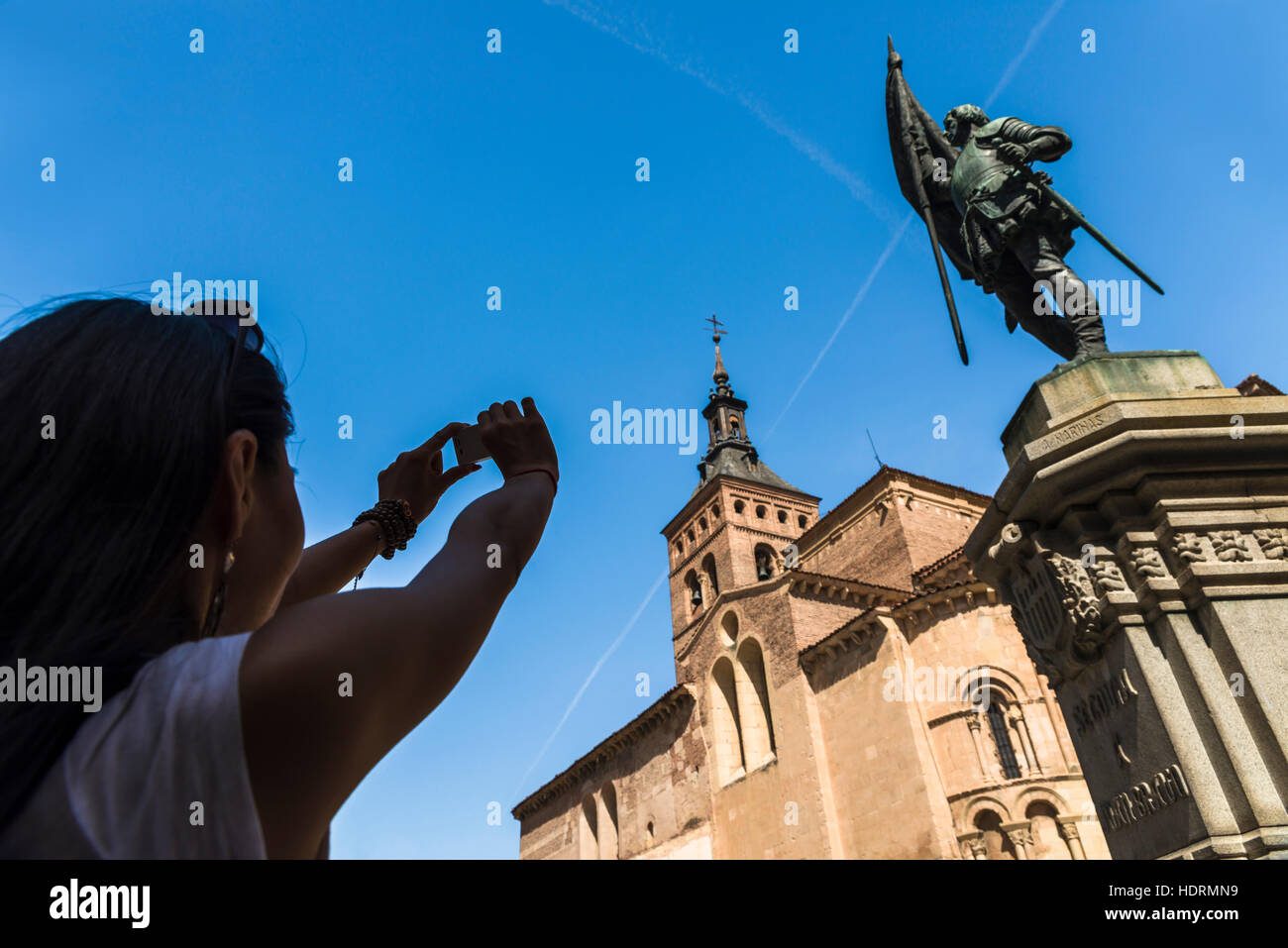 An asian young woman taking a picture of San Martin Church and Juan Bravo statue, Romanic style construction; Segovia, - Stock Image