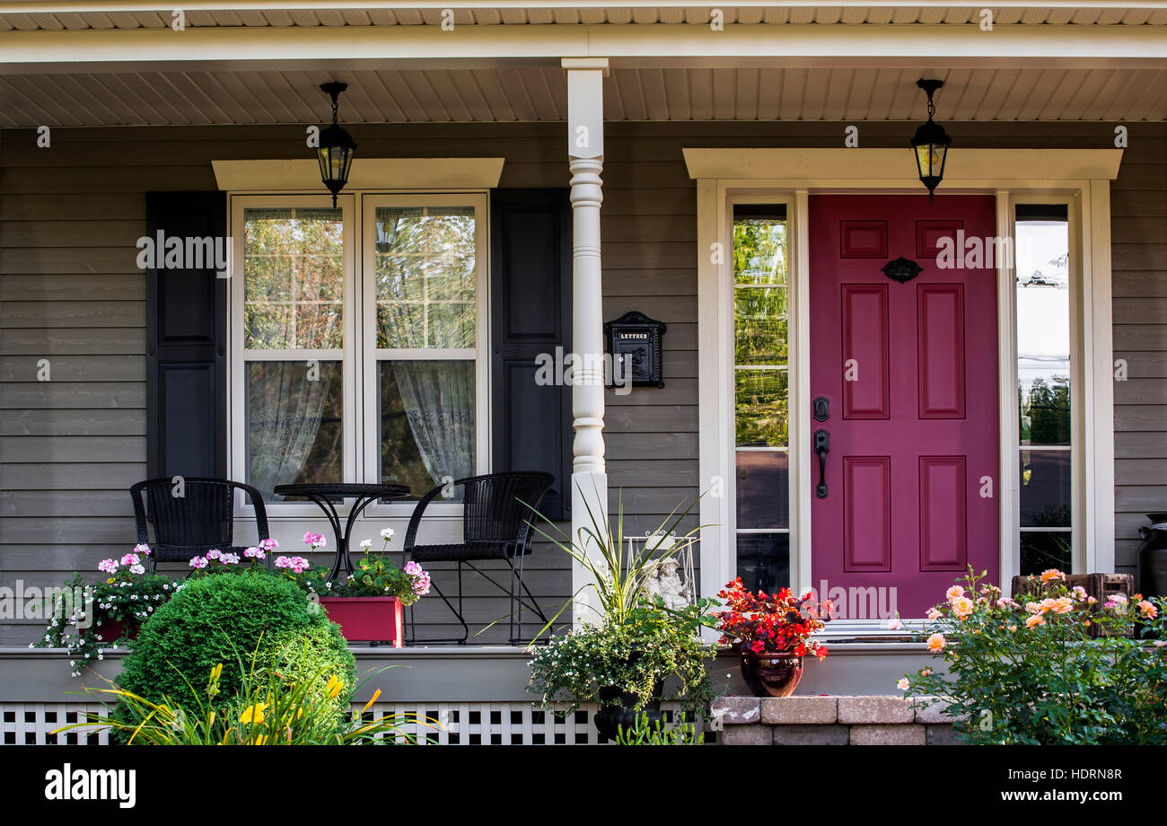 Front porch of a house with decorative plants and flowers and a red door knowlton quebec canada