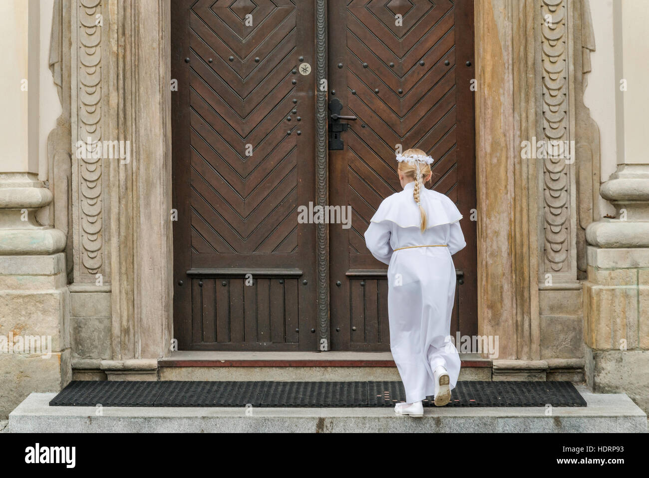 Girl entering church for First Holy Communion event, Cathedral Basilica in Lowicz, Mazovia, Poland - Stock Image