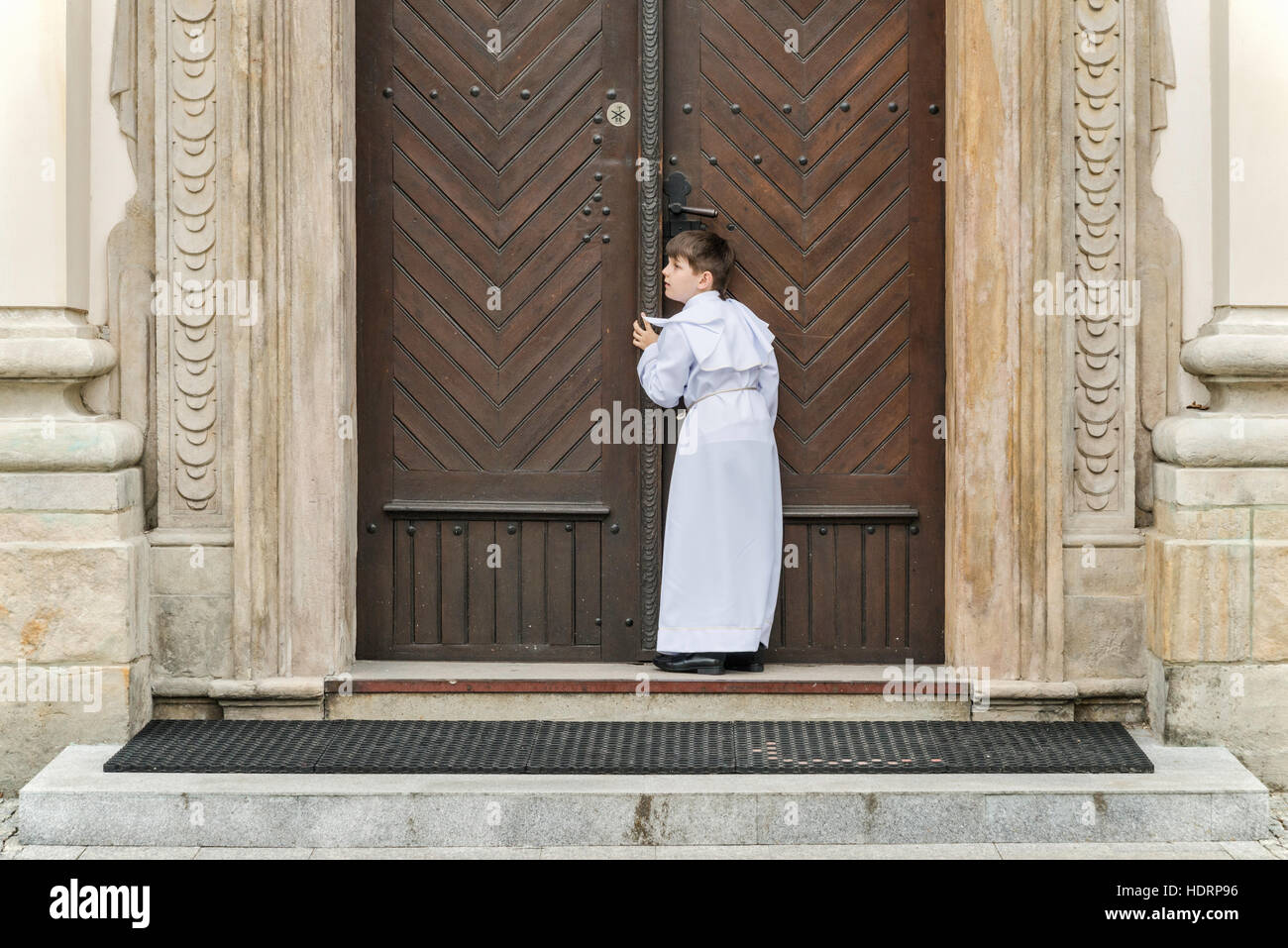 Boy entering church for First Holy Communion event, Cathedral Basilica in Lowicz, Mazovia, Poland - Stock Image