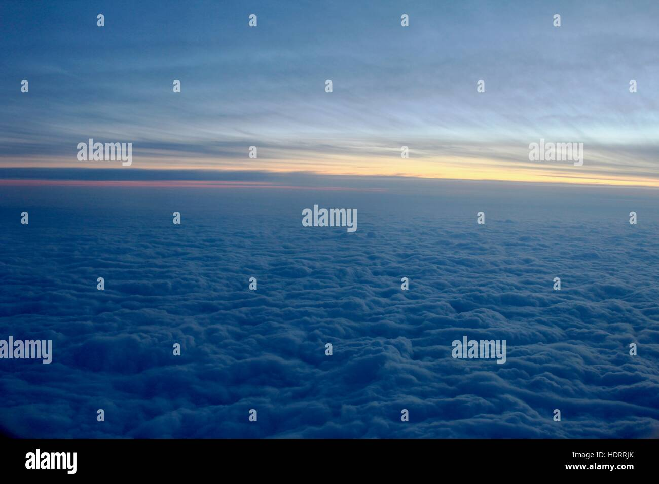 The view from outside the airplane window above clouds during winter and sunset. - Stock Image