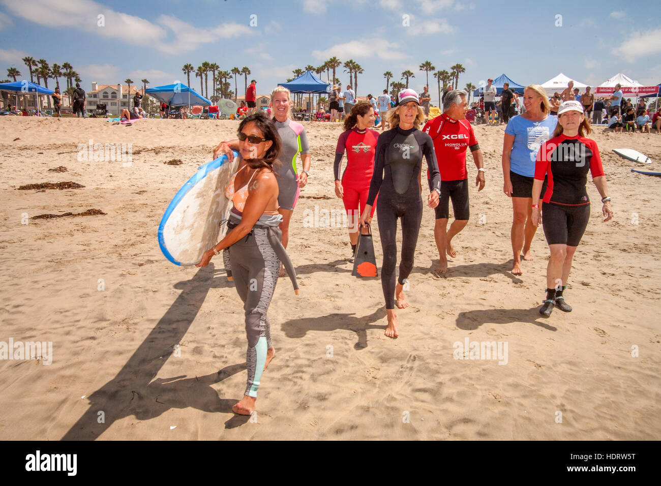 In thanks for his military service, a veteran (center right) receives a free surfing lesson from a female instructor - Stock Image