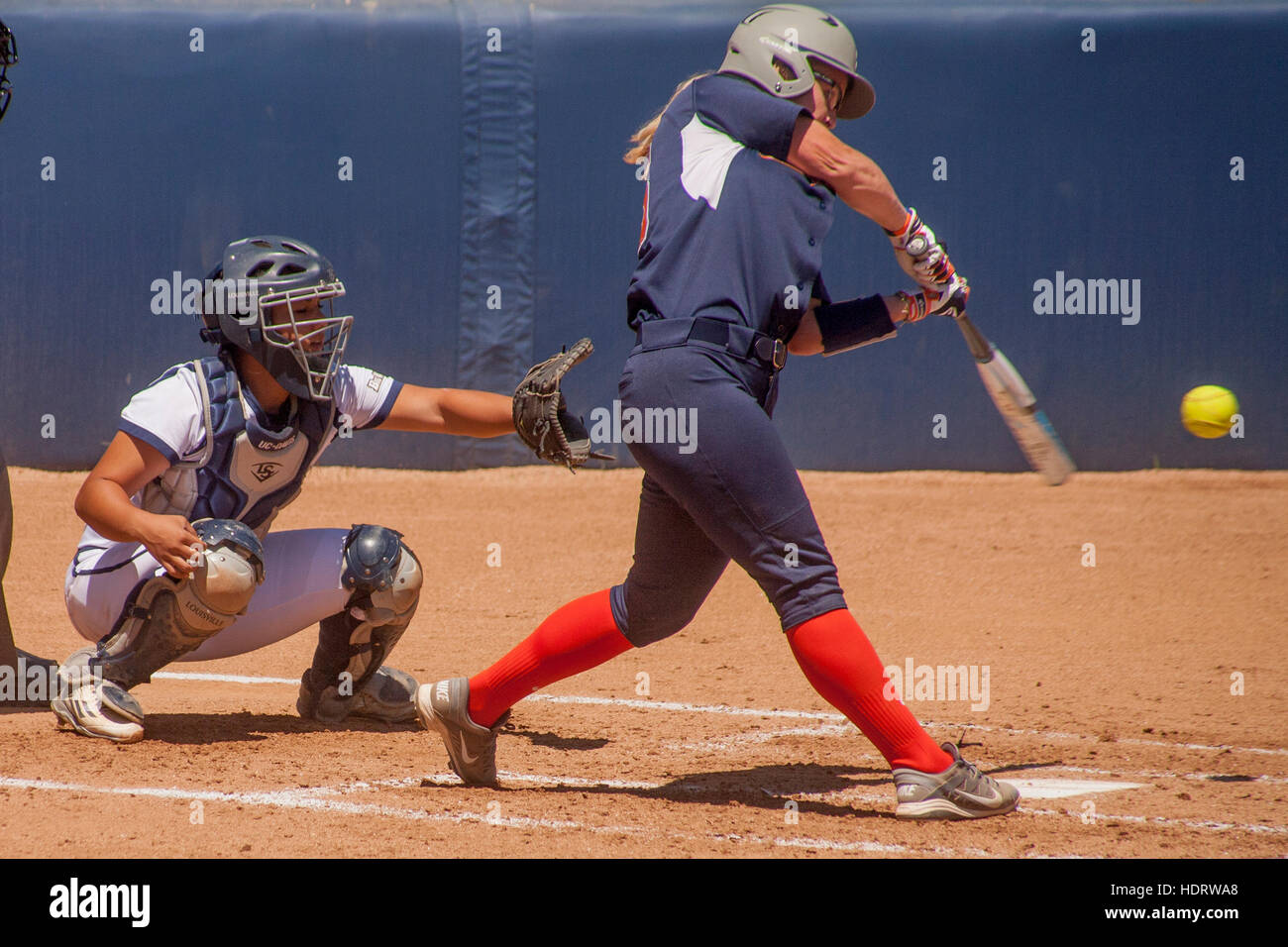 Up at bat, a college woman softball player swings at the ball at a game on the field in Fullerton, CA. Note batting - Stock Image