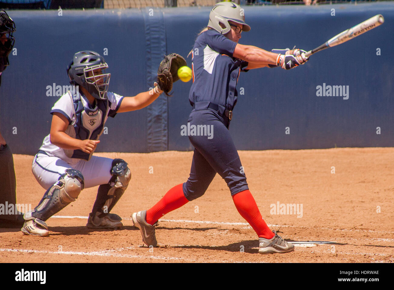 Up at bat, a college woman softball player swings at the ball and misses at a game on the field in Fullerton, CA. - Stock Image
