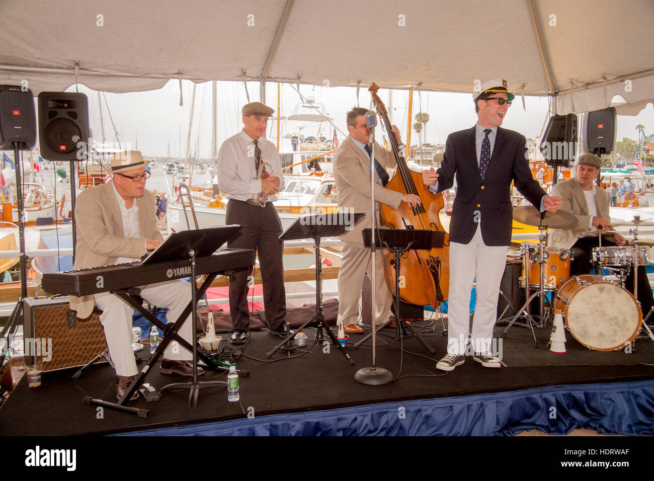 Its singer decked out in a yachting cap, a band entertains visitors to an exhibition of vintage wooden boats at - Stock Image