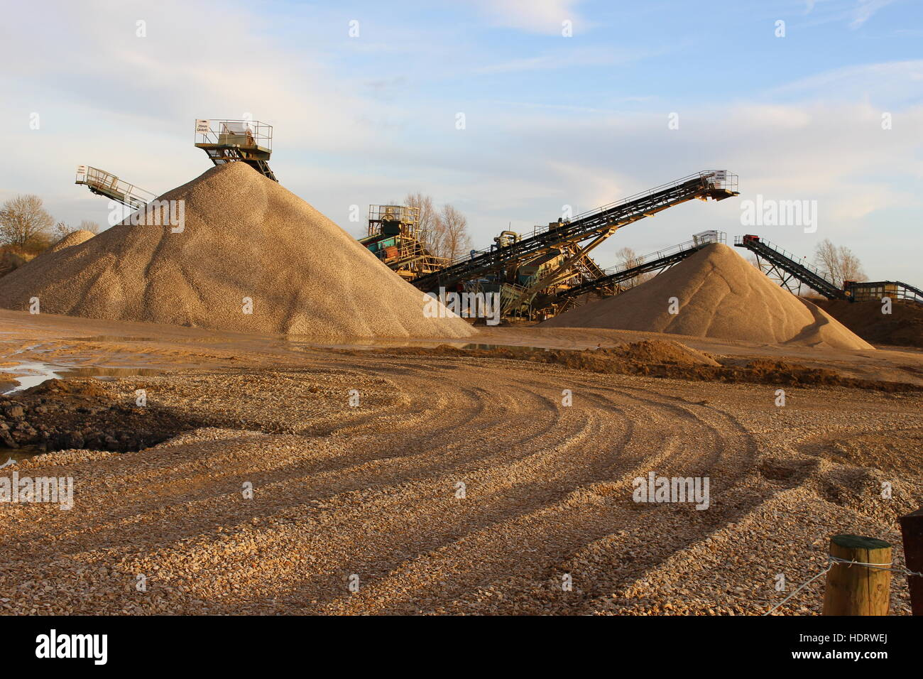 Quarry heaps piles gravel sand bulk rock mineral aggregate machinery machines crusher grinder grinding tyre tracks - Stock Image