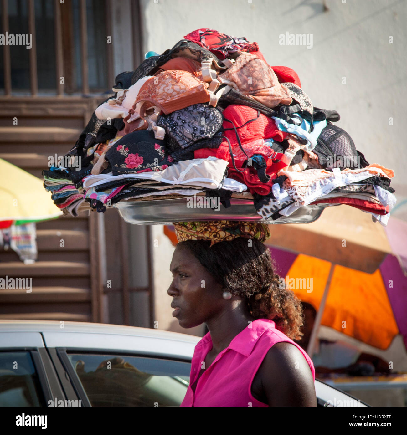 Woman carrying a tray full of bras on her head Stock Photo