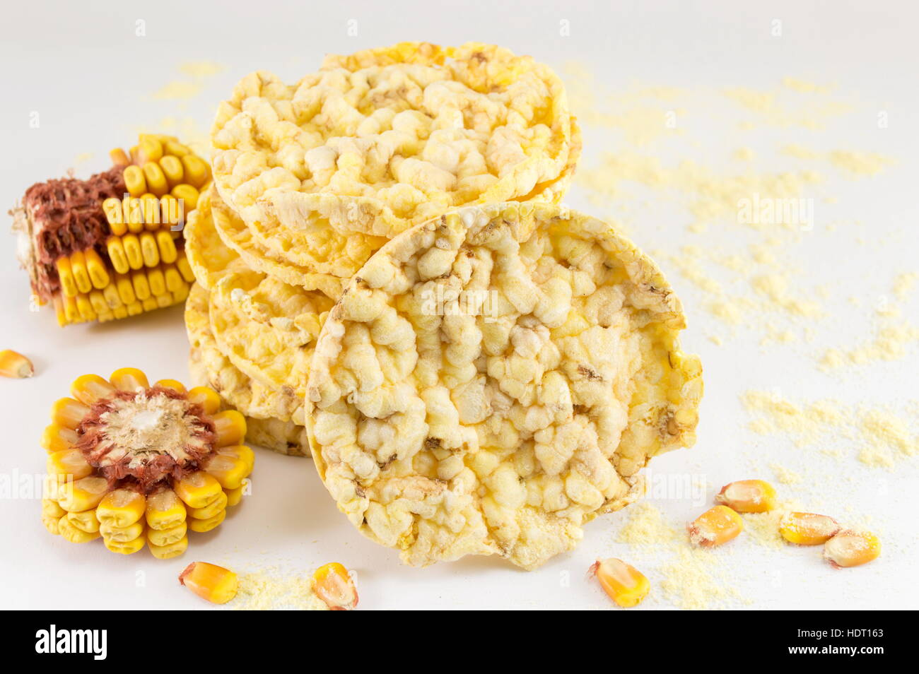 circle shaped corn snacks and corn kernels - Stock Image
