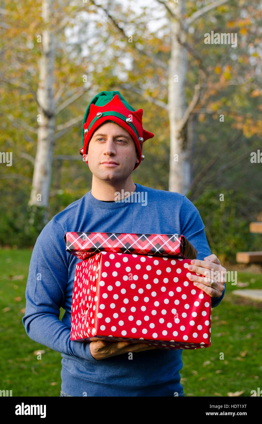 Man holding Christmas presents reminiscing about the Holiday season. - Stock Image