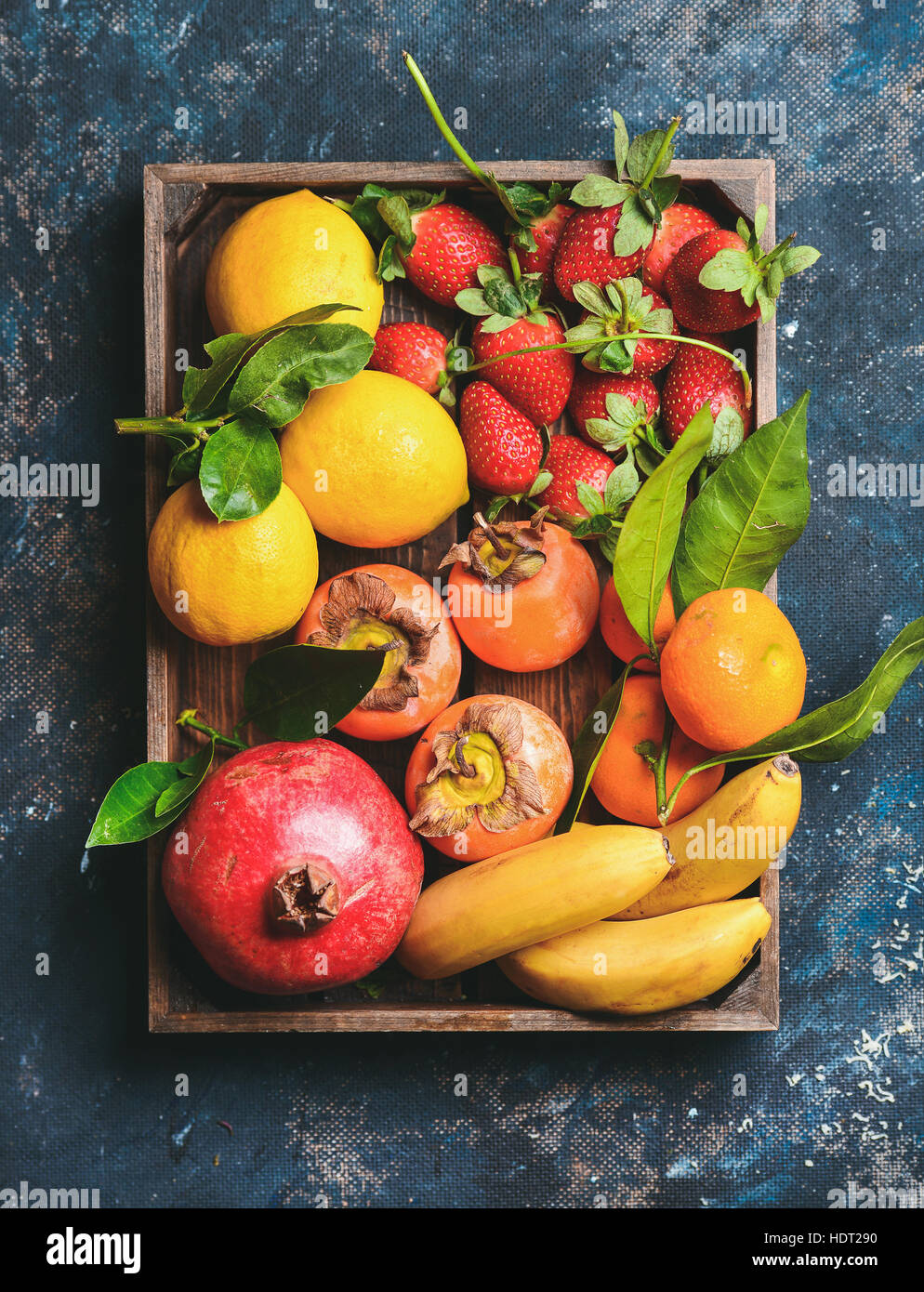 Oranges, lemons, pomegranate, bananas, strawberries and persimmon in wooden box - Stock Image
