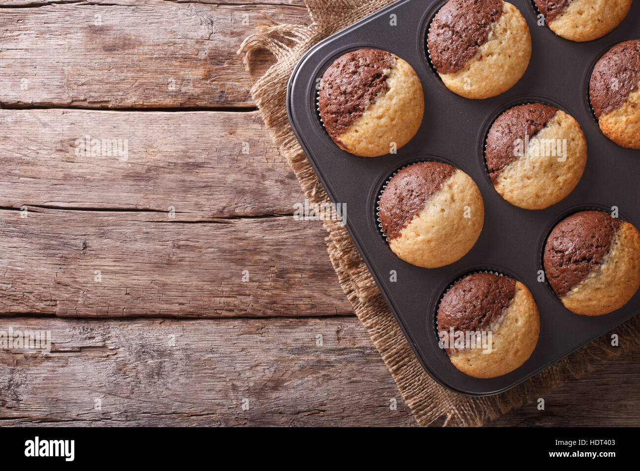 hot colorful cupcakes in a baking dish. horizontal view from above - Stock Image