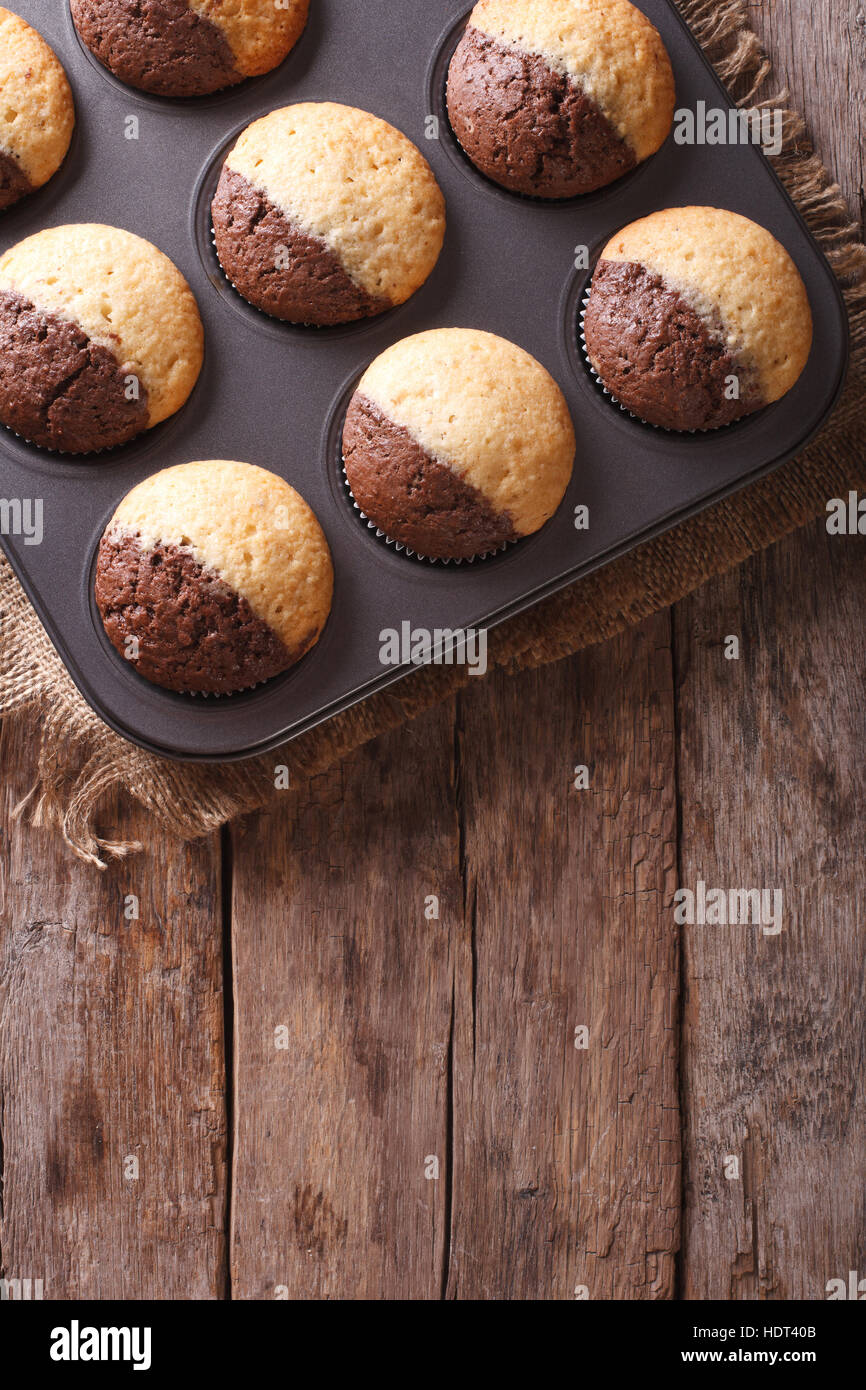 chocolate-orange muffins in baking dish from the oven. vertical top view - Stock Image