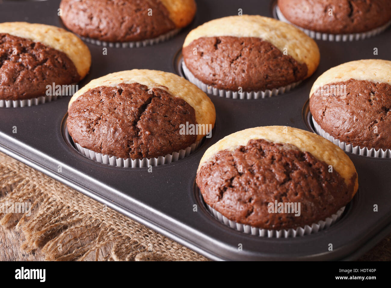 fresh chocolate muffins in baking dish from the oven closeup. Horizontal - Stock Image