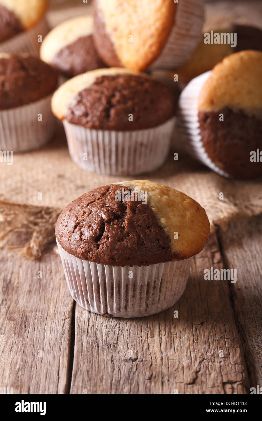beautiful two-tone chocolate muffins on a table close-up, vertical - Stock Image