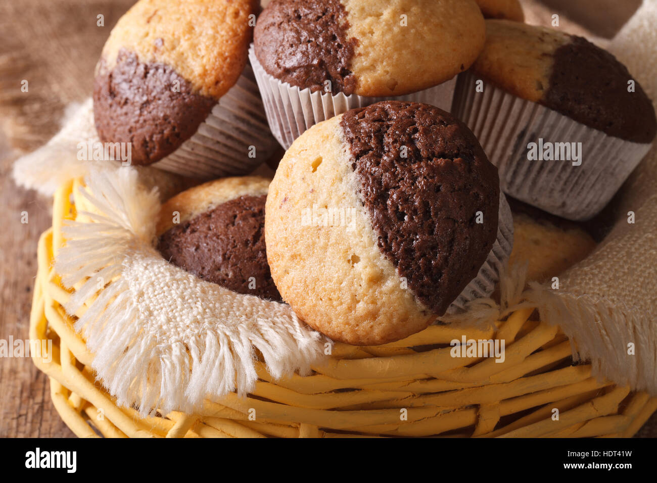 two-tone muffins orange and chocolate close-up in a basket. horizontal - Stock Image