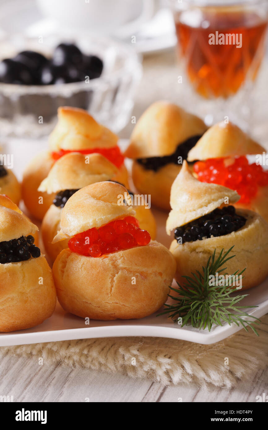 Tasty snack: profiteroles stuffed with red and black caviar on a plate close-up. vertical - Stock Image