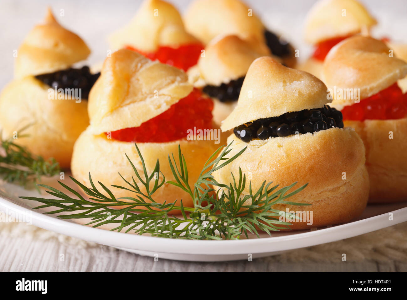 Finger food: profiteroles stuffed with red and black caviar on a plate close-up. horizontal - Stock Image