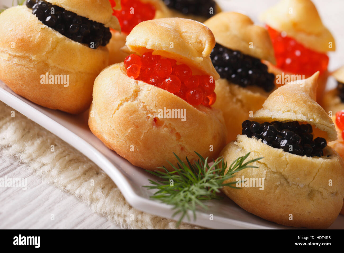 Fresh profiteroles stuffed with red and black caviar on a plate close-up. Horizontal - Stock Image