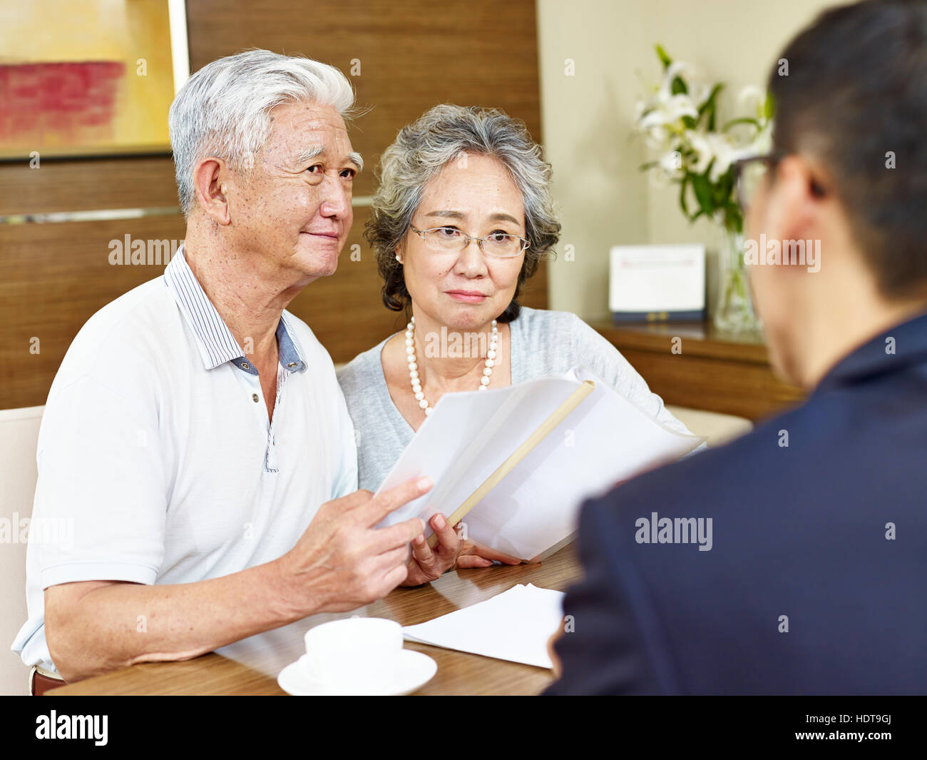 senior asian couple appear to be skeptical after reading a proposal - Stock Image